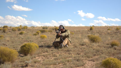 A shooter uses a makeshift bipod to steady their rifle for a long shot.